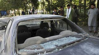 Afghan men look at a damage car after a roadside bomb explosion in Kabul, Afghanistan, Sunday, June 6, 2021.