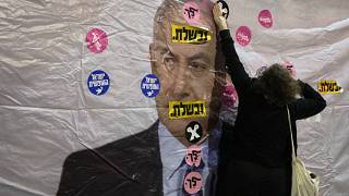"""محتج إسرائيلي يضع ملصقا على صورة بنيامين نتنياهو خلال مظاهرة نظمت أمام منزله في القدس وقد كتب عليها بالعبرية: """"لقد فشلت""""، """"ارحل"""". 2021/06/05"""