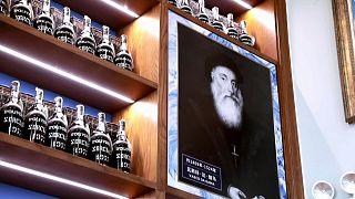 """Retrato do navegador Vasco da Gama entre as garrafas exibidas na loja """"Madeira Home"""""""