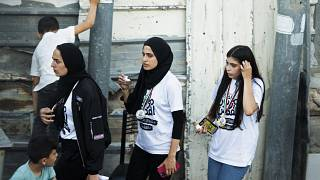 In this Friday, June 4, 2021 photo, Palestinian activist Muna el-Kurd, centre, wears a medal from a marathon as she leaves the site where Israeli police fired tear gas.