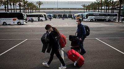 Passengers wearing face masks arrive at Palma de Mallorca Airport on the Spanish Balearic Island of Mallorca, Spain, Saturday, March 27, 2021.