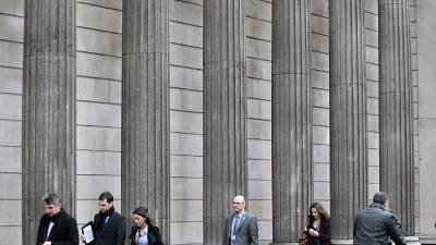 People walk past the Bank of England in the City of London's financial district
