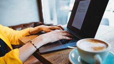 Digital nomad works on a laptop in a café.