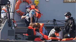 A Border Force official lifts a child from a small boat arriving in the port of Dover in August 2020