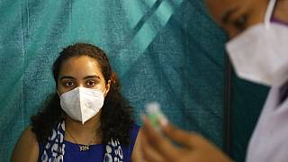 A woman waits to receive a dose of Covishield, the Oxford-AstraZeneca vaccine for COVID-19, in Ahmedabad, India, Saturday, June 5, 2021