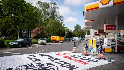 Protestors covered in black paint take part in an action called by global environmental movement Extinction Rebellion, at a Shell gas station in The Hague.