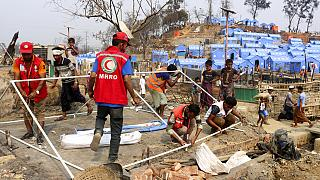 Volunteers help rebuild after a huge fire at a refugee camp for Rohingya Muslims in March: one of the locations set to be affected by the cuts