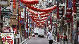 رجل ياباني يضع كمامة على وجهه في قناع كإجراء وقائي ضد فيروس كورونا ويسير في منطقة  تشاينا تاون التجارية والسياحية قرب طوكيو والخالية من السيّاح والعمال بسبب جائحة كورونا