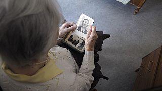 anziana donna che guarda una sua foto da giovene