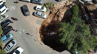 انهيار أرضي يتسبب بحفرة هائلة في موقف للسيارات أمام مستشفى - القدس