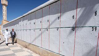 جزائريان يمران بجانب حائط محصص لملصقات المرشحين الانتخابيين