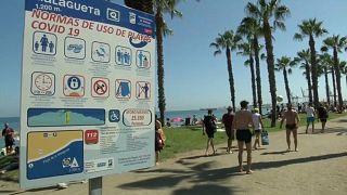 Ein Strand in Málaga mit einem Hinweisschild für die Corona-Regeln