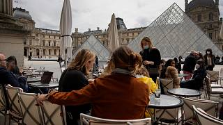 People drink outdoors on a bar terrace in front of the Louvre museum in Paris, Thursday, May 20, 2021.