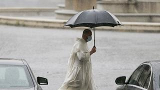 A priest is pictured walking through unusually heavy rainfall that hit Rome on Tuesday.