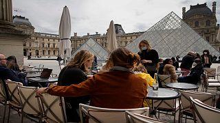 أشخاص يجلسون في شرفة إحدى المقاهي المطلة على متحف اللوفر وسط العاصمة الفرنسية باريس.