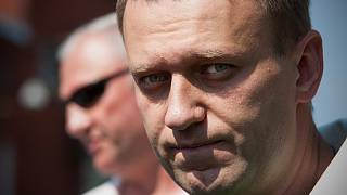 Russian protest leader Alexei Navalny leaves the headquarters of the Russian Investigation committee in Moscow, Russia, Friday, Aug. 3, 2012.