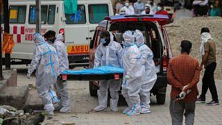 Hindistan'da Covid-19 nedeniyle hayatını kaybeden bir kişinin bedeni yakılmak üzere krematoryuma götürülürken