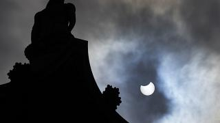 The partially eclipsed sun beside Nelson's Column in Trafalgar Square in London, Thursday, June 10, 2021.