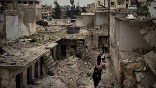 Suriye'nin İdlib kentinde, yoğun bombardıman sonucu harabeye dönen bir mahalleden geçen kadınlar (arşiv)
