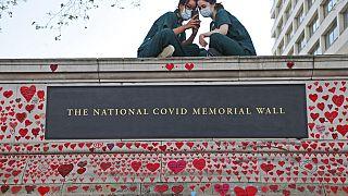 Londra, giugno 2021: infermiere dell'ospedale St Thomas riposano sul muro del memoriale nazionale per le vittime di Covid