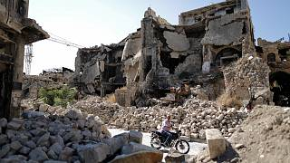 FILE: In this Saturday, July 27, 2019 photo, a man rides his motorcycle through the rubble of the old city of Aleppo, Syria.