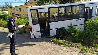 A Russian police officer stands near the damaged bus.
