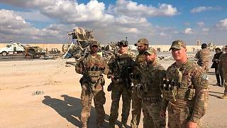 U.S. Soldiers stand at a site of Iranian bombing at Ain al-Asad air base