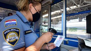 Horvát határőr szkenneli a Covid-igazolvány kódját a horvát-szlovén határon