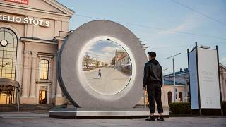 A young man stands in front of a one of two hi-tech 'portals' installed in Lulblin, Poland and Vilnius, Lithuania which give passers by a real-time look at life in each city,