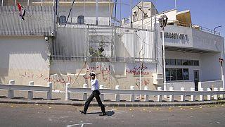 Un policía camina frente a la embajada estadounidense dañada después de que manifestantes progubernamentales atacaran la embajada en Damasco