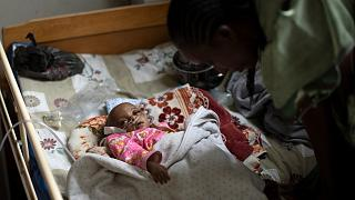 Malnourished baby Mebrhit, who at 17 months old weighs just 5.2kg (11lbs 7oz), being cared for by her mother Birhan Etsana, at a Tigray hospital on May 10, 2021