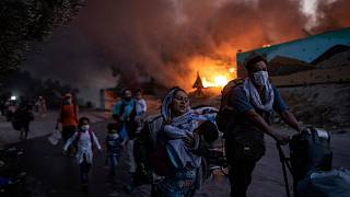 migrants flee from the Moria refugee camp during a second fire