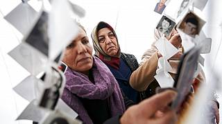 Women look at images of victims inside a traveling monument called 'Prijedor 92' outside the Yugoslav War Crimes Tribunal, ICTY