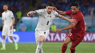 Italy's Jorginho, left, fights for the ball with Turkey's Irfan Kahveci during the first Euro 2020 match at the Olympic stadium in Rome, Friday, June 11, 2021