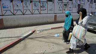 جزائريات يسرن بجانب ملصقات دعائية انتخابية