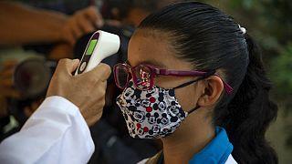 Meksika'da sınıfa girmeden önce ateşini ölçtüren kız çocuğu