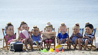 Activistas climáticos de Oxfam, con cabezas gigantes que representan a los líderes del G7 en la playa de Swanpool en Falmouth, Cornualles, Inglaterra, el 12 de junio de 2021.