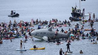 Paddleboarders and surfers take part in a paddle out to raise awareness for climate action in the sea at Gyllyngvase Beach in Falmouth, Cornwall, England, June 12, 2021.
