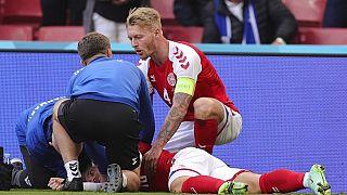 Eriksen es atendido por sus compañeros en el terreno de juego, después de desmayarse