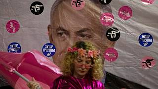An Israeli protester wears pink during a demonstration against Israeli Prime Minister Benjamin Netanyahu outside his official residence in Jerusalem, Saturday, June 12, 2021.