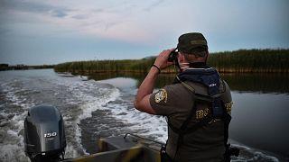 ضابط شرطة يقوم بدوريات في نهر إيفروس على متن قارب على طول الحدود اليونانية التركية، 8 يونيو 2021