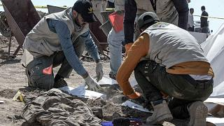 براء الطب الشرعي يفحصون رفات بشرية بعد اكتشافهم مقبرة جماعية في قرية بادوش شمال العراق تعود لضحايا مذبحة سجن بادوش عام 2014 التي ارتكبها تنظيم الدولة الإسلامية، 13 يونيو 2021