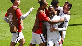 England's Raheem Sterling, centre, is congratulated by teammates after scoring his team's first goal during Euro 2020