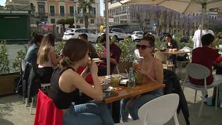 People enjoy a coffee outside in a restaurant in Sardinia, Italy