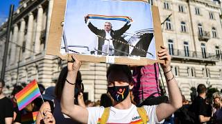 A participant holds a placard showing Hungarian Prime Minister Viktor Orban holding a scarf in rainbow colours, in front of the parliament building in Budapest on June 14