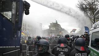 File - In this Wednesday, Nov. 18, 2020 file photo, police uses water canons as people attend a protest rally against coronavirus restrictions in Berlin, Germany.