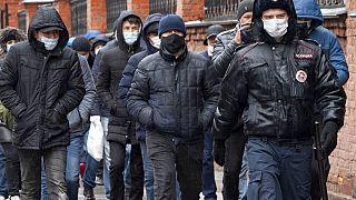 Полицейский сопровождает группу мигрантов.