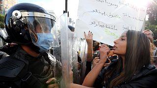Januári felvétel: kormányellenes tüntető rúzsozza magát egy rohamrendőrrel szemben állva Tuniszban