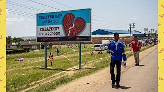 Des personnes passent devant un panneau d'affichage de sensibilisation de la AIDS Healthcare Foundation à Maputsoe, au Lesotho, le 31 janvier 2020