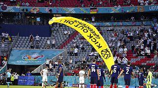 Il paracadutista di Greenpeace atterra in campo, in mezzo ai giocatori di Germania e Francia, pronti a disputare la partita